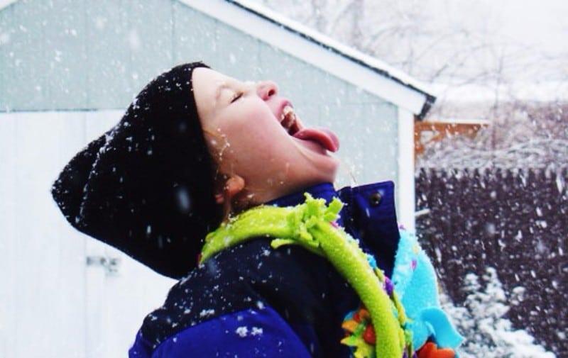 Criança com boca aberta comendo neve
